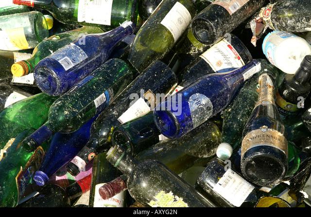Old green and blue glass bottles at recycling plat / Grüne und blaue Altglasflaschen in Sammelstelle - Stock Image