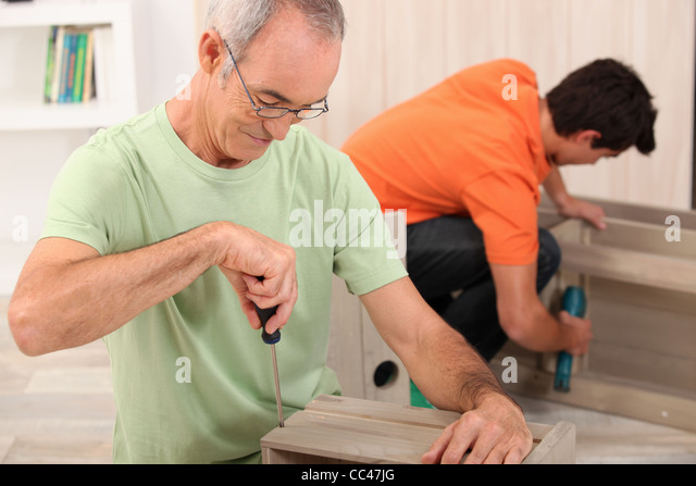 Attractive Father And Son Putting Together Flatpack Furniture   Stock Image