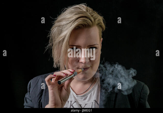 Woman smoking thin electronic cigarette and looking at in the camera - Stock Image
