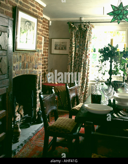 Country Dining Room With Brick Wall Above Fireplace And Crockery Cutlery On The Table