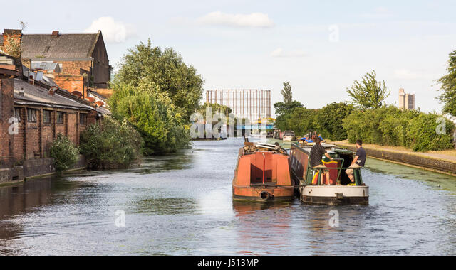 London, England - July 10, 2016: Traditional narrowboats on the Grand Union Canal pass derelict industrial units - Stock Image