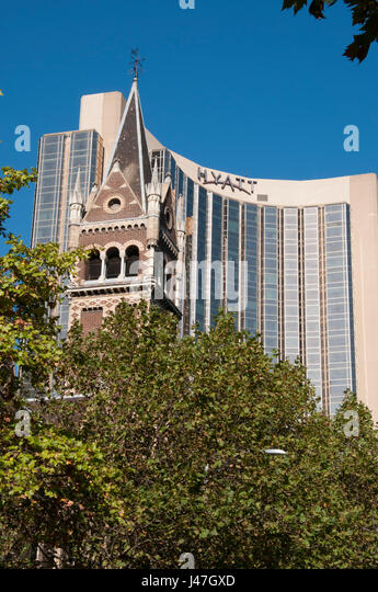 Spire of St Michael's Uniting Church (1867) with the upscale Grand Hyatt Hotel beyond - Stock Image
