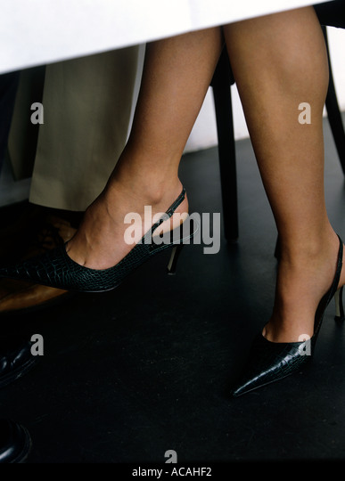 pair of women s legs under the table in a restaurant - Stock Image