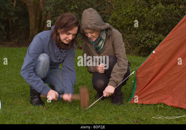 Two girls c&ing hammering in a tent peg attached to the guy ropes of a pup  sc 1 st  Alamy : guy pitching a tent - memphite.com