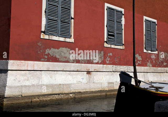 a beautiful terracotta red wall with the paint pealing off in a canal in venice - Terracotta Wall Paint