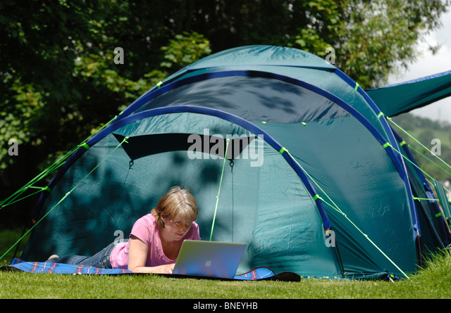 A woman lying on a blanket outside a green tent on a c&site using a laptop & Woman Outdoors Laptop Computer Tent Working Lady Female Technology ...