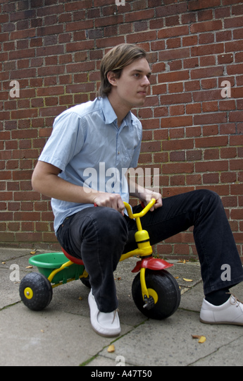 young man riding small childrens toy tricycle or bike stock image - Small Childrens Images