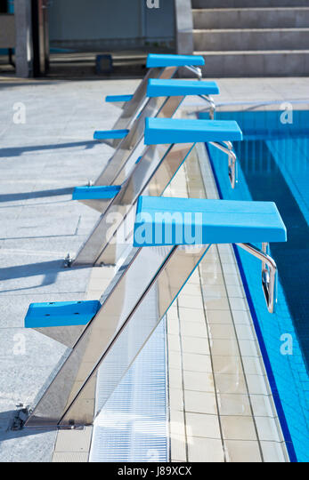 starting blocks in a row at the edge of swimming pool outdoors selective focus