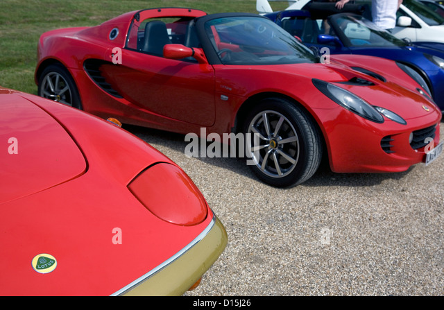 A Row Of Modern And Old Lotus Cars Parked On Gravel At A Car Show.