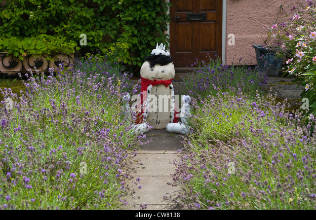Effigy of King Pin on lavender path in garden at village fete on Scarecrow Day in