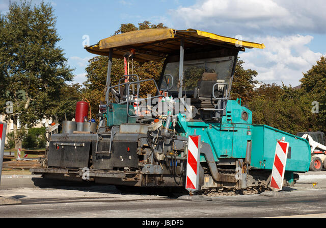 asphalt paving machine at construction sito on a street stock image