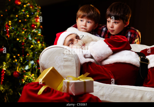 photo of santa claus sleeping on sofa with two amazed kids near by stock image