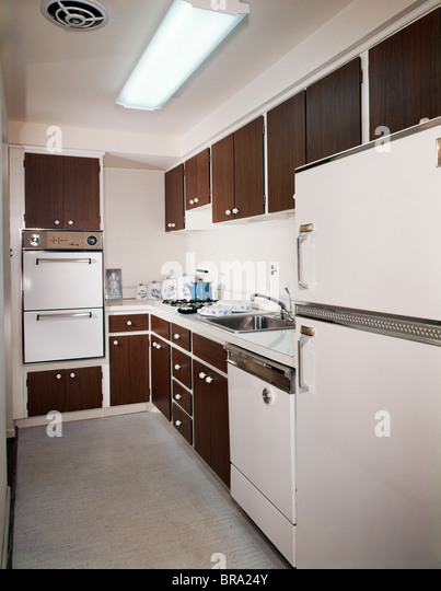 1970s narrow galley style kitchen with dark wooden cabinets and white appliances   stock image kitchen appliances classic stock photos  u0026 kitchen appliances      rh   alamy com