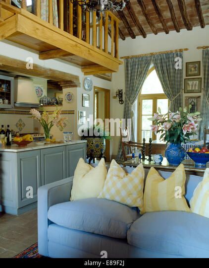Yellow Cushions On Pale Blue Sofa In Open Plan Italian Living Room With Mezzanine Balcony Above