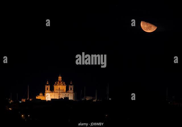 Rising moon above the parish church of Zejtun, Malta, Europe - Stock Image