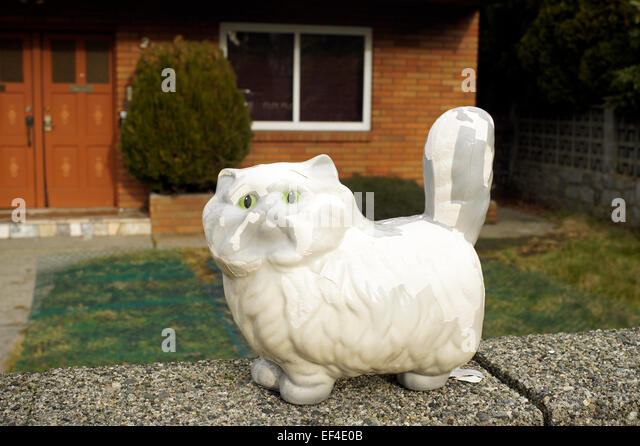 white-ceramic-cat-figure-standing-on-a-s