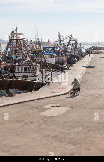 A man cycles down the quiet docks of the new port in Essaouira, Morocco - Stock Image