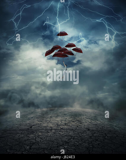 Young man with a lot of umbrellas as an air balloon rise up to the sky full of lightnings, above the cracked desert - Stock Image