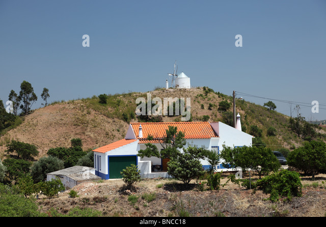 rural house and windmill in portugal stock image