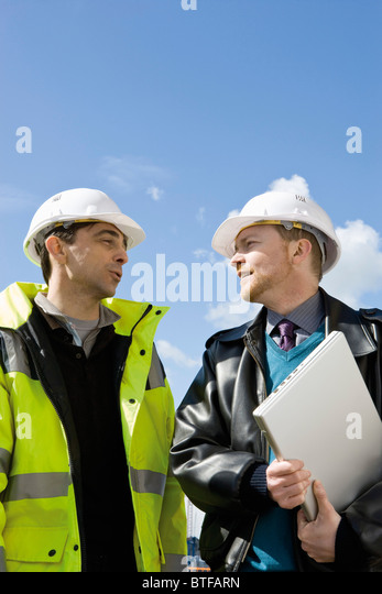 Hard hats building plans stock photos hard hats building for My contractor plan