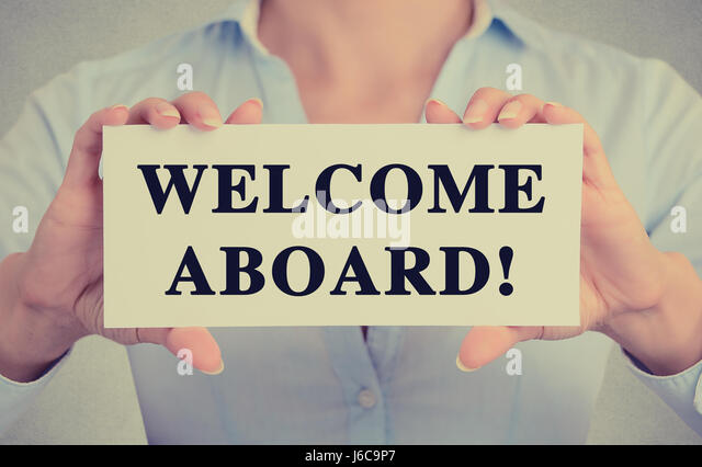 Businesswoman hands holding white card sign with welcome aboard text message isolated on grey wall office background. - Stock Image