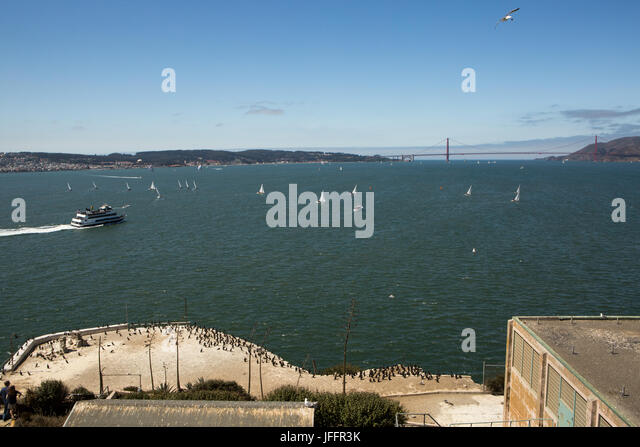 A view from the Alcatraz Federal Penitentiary of sailboats, tour boats, and the Golden Gate Bridge. - Stock Image