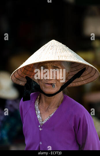 Elderly vietnamese woman wearing a conical hat at her market stall in
