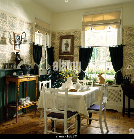 White Chairs At Table In Eighties Dining Room With A Roman Blind And Blue Drapes On