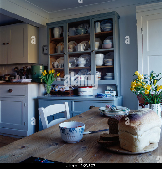 Loaf Of Bread On Old Wood Table In Kitchen Dining Room With Fitted Blue Dresser