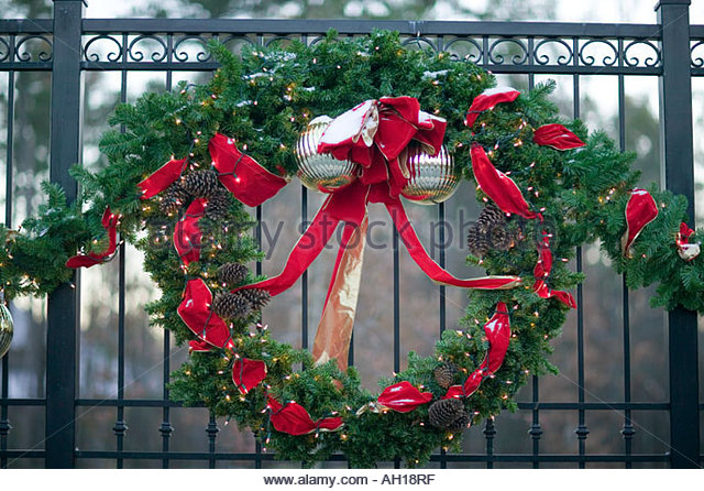 christmas decorations hanging on a fence outside a gated community in arkansas stock image