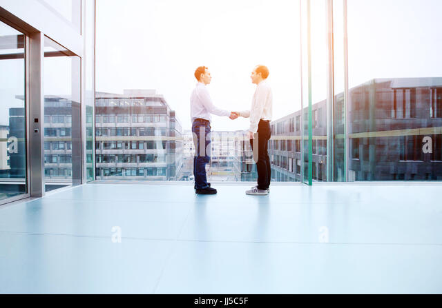 business cooperation concept, collaboration, two business people shaking hands in office interior - Stock Image