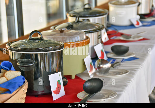 Row of crock pots with ladles in a chili cook off contest in a