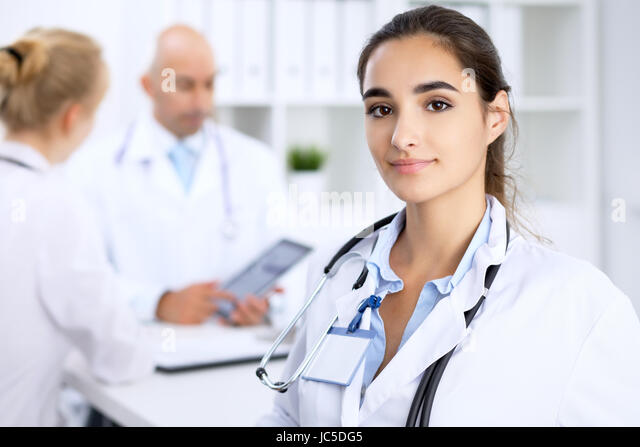 Female doctor smiling on the background with patient and his physician in hospital - Stock Image