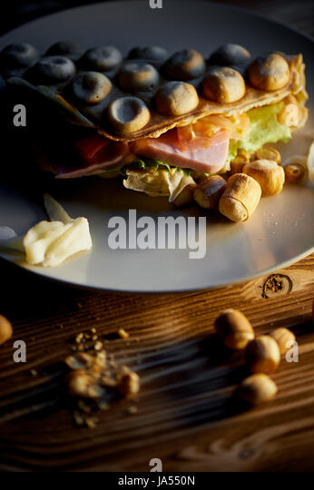 Rich Hong Kong waffle with cheese, ham, lettuce, tomato. On dark wooden background. Scattered nuts and dried squid - Stock Image