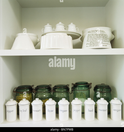 Close Up Of Collection Of White Ceramic Kitchen Storage Jars On White  Shelves With Green