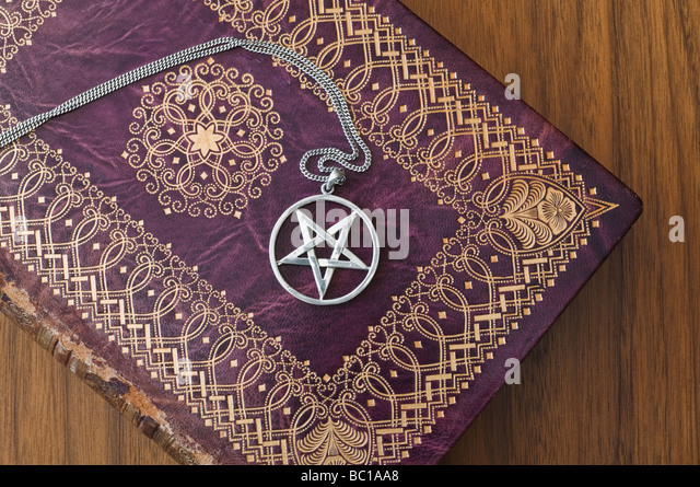 Silver Necklace With Inverted Pentagram On An Old Book.   Stock Image