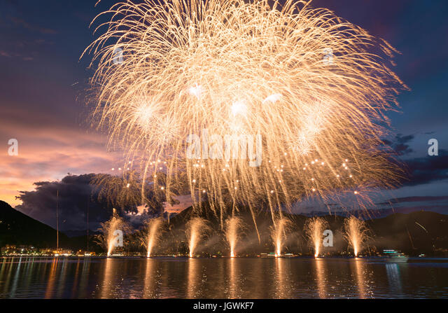 Fireworks on the Lugano Lake in a summer evening with cloudy sky at the sunset in the background - Stock Image