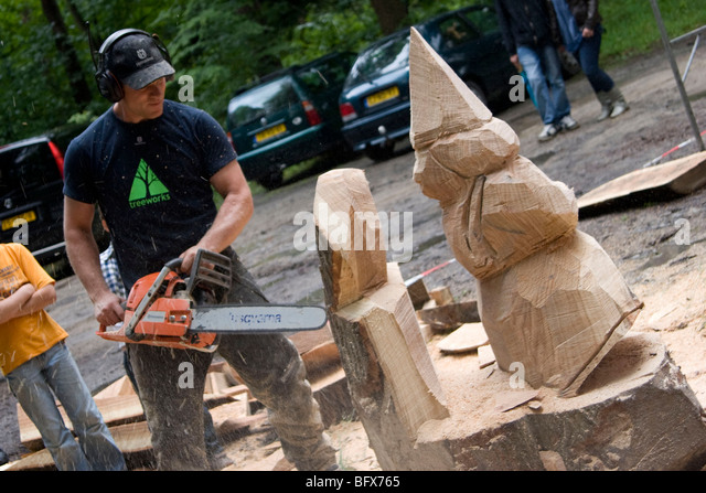 Man chainsaw carving stock photos