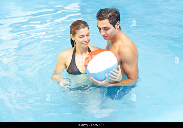 Pool Water With Beach Ball attractive couple playing beach ball stock photos & attractive