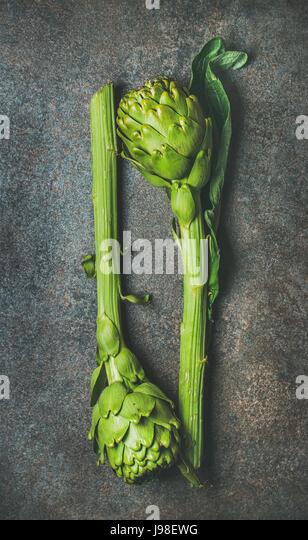 Fresh raw green artichockes over dark stone background, top view - Stock Image