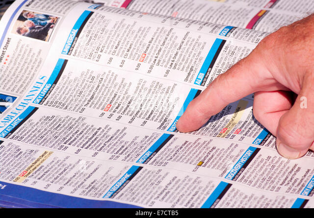 tv listings. mans finger on a television listings tv listing guide magazine - stock image tv
