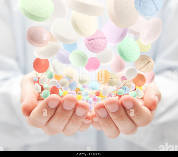 Colorful pills falling into open palms - Stock Image
