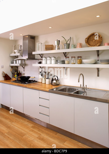 Stainless Steel Sink In Fitted White Unit Below White Shelves In Modern Kitchen Stock Image