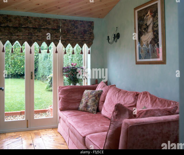 Pink Velvet Sofa In A Blue Nineties Living Room With A Tasseled Roman Blind  On Glass