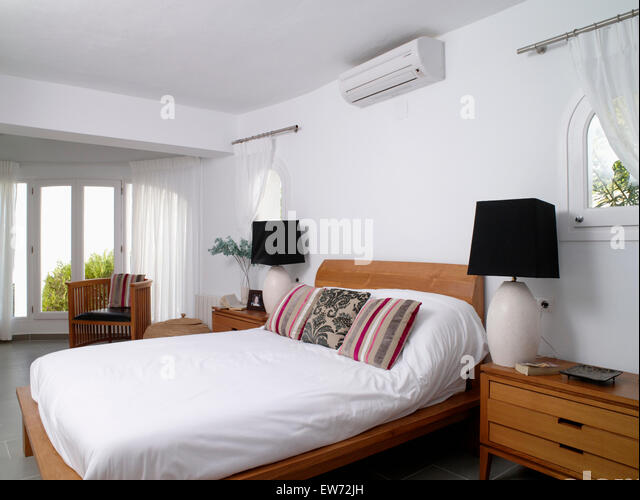 Small air conditioning unit above bed with white duvet and striped cushions  in modern white. Modern Monochromatic Lighting Furniture Stock Photos   Modern