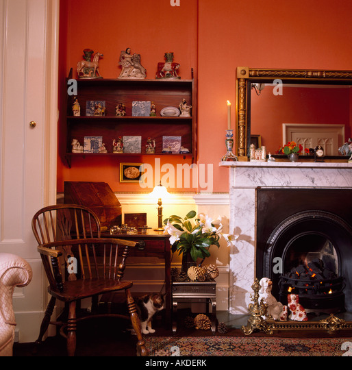 wooden shelving in alcove beside fireplace in red living room with antique windsor chair stock