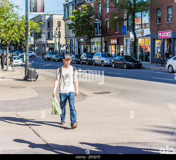 Montreal, Canada - May 27, 2017: Young man crossing street on Saint Laurent boulevard in Montreal's Plateau - Stock Image