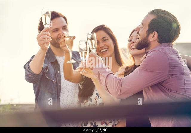 Friends drinking champagne together outdoors - Stock Image