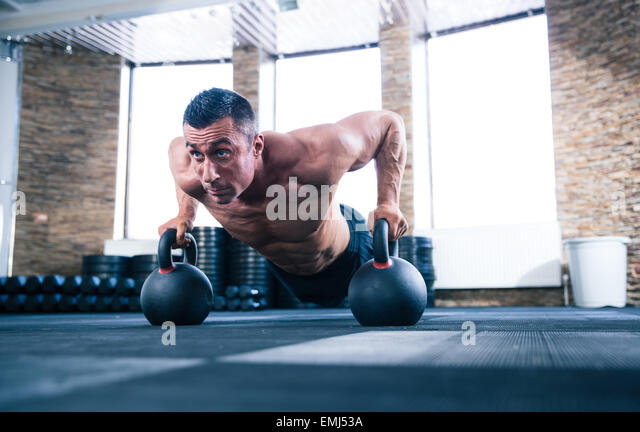 Bodybuilder doing push ups in stock photos