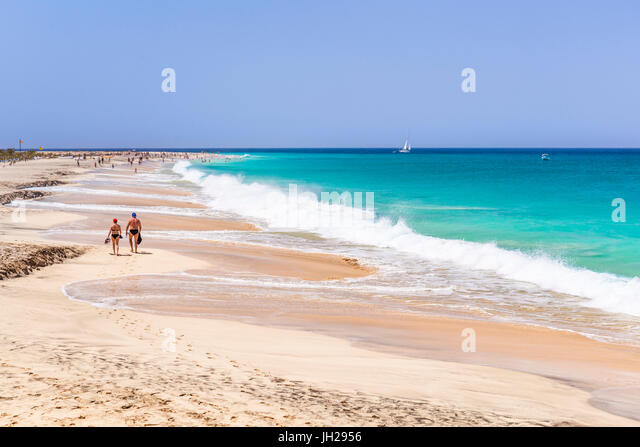 Tourists walking along the sandy beach, Ponta Preta beach, Santa Maria, Sal Island, Cape Verde, Atlantic, Africa - Stock Image